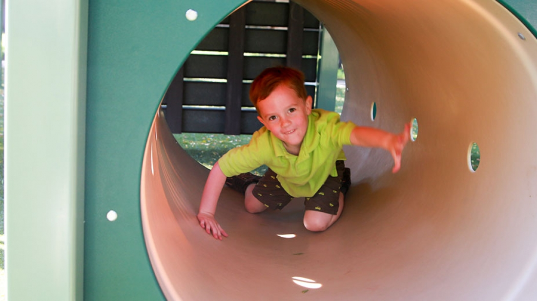 boy playing in tunnel